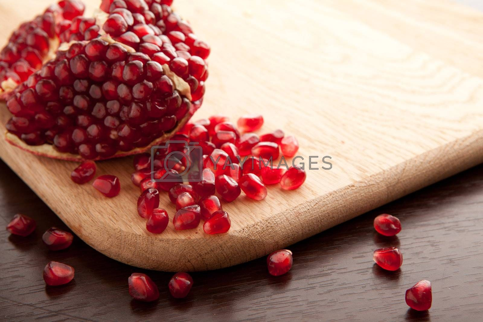Pomegranate slices and handful of seeds on wooden background with empty place for text