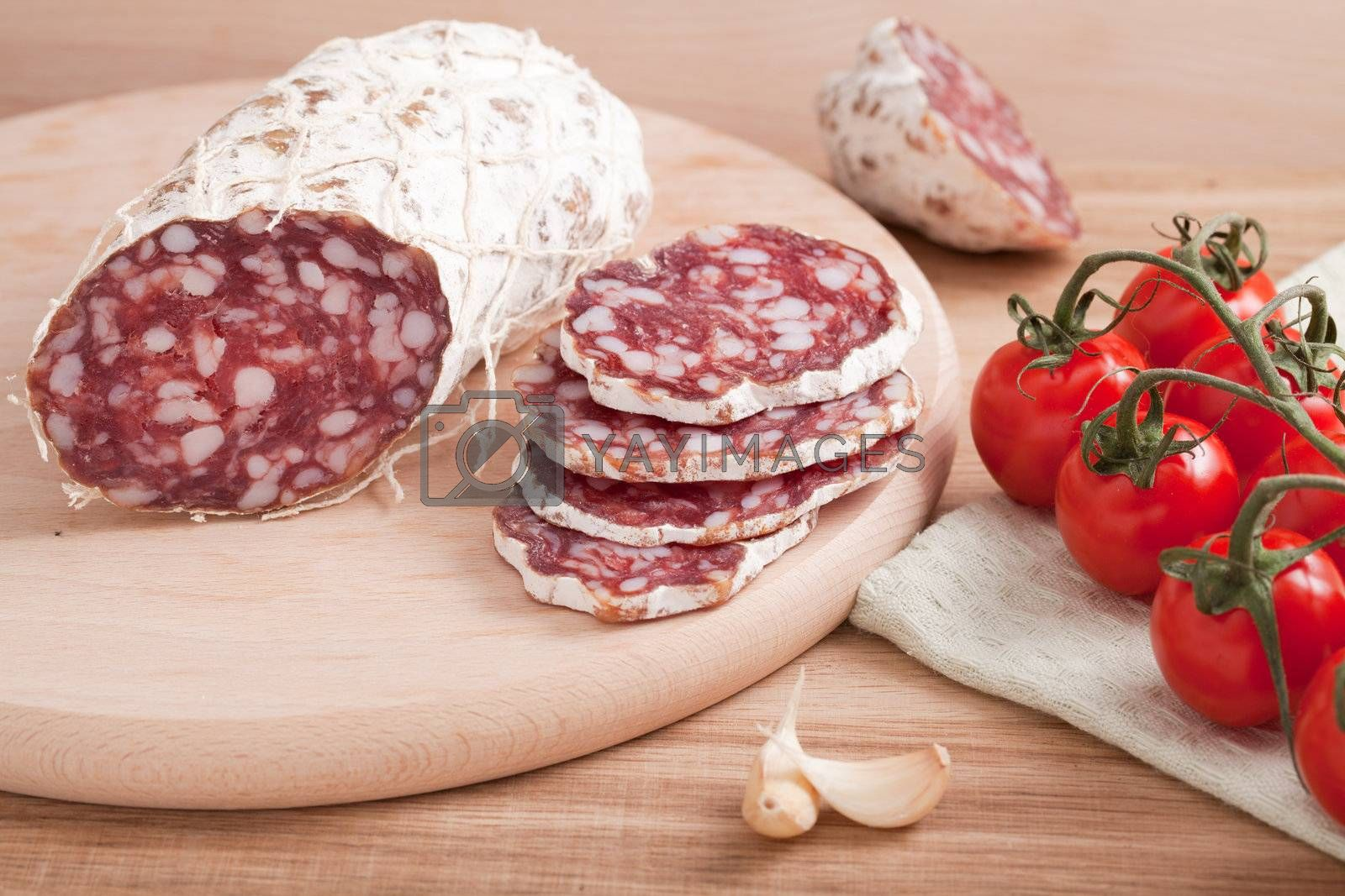 Traditional sliced salami on wooden board with garlic, cherry to by SergeyAK