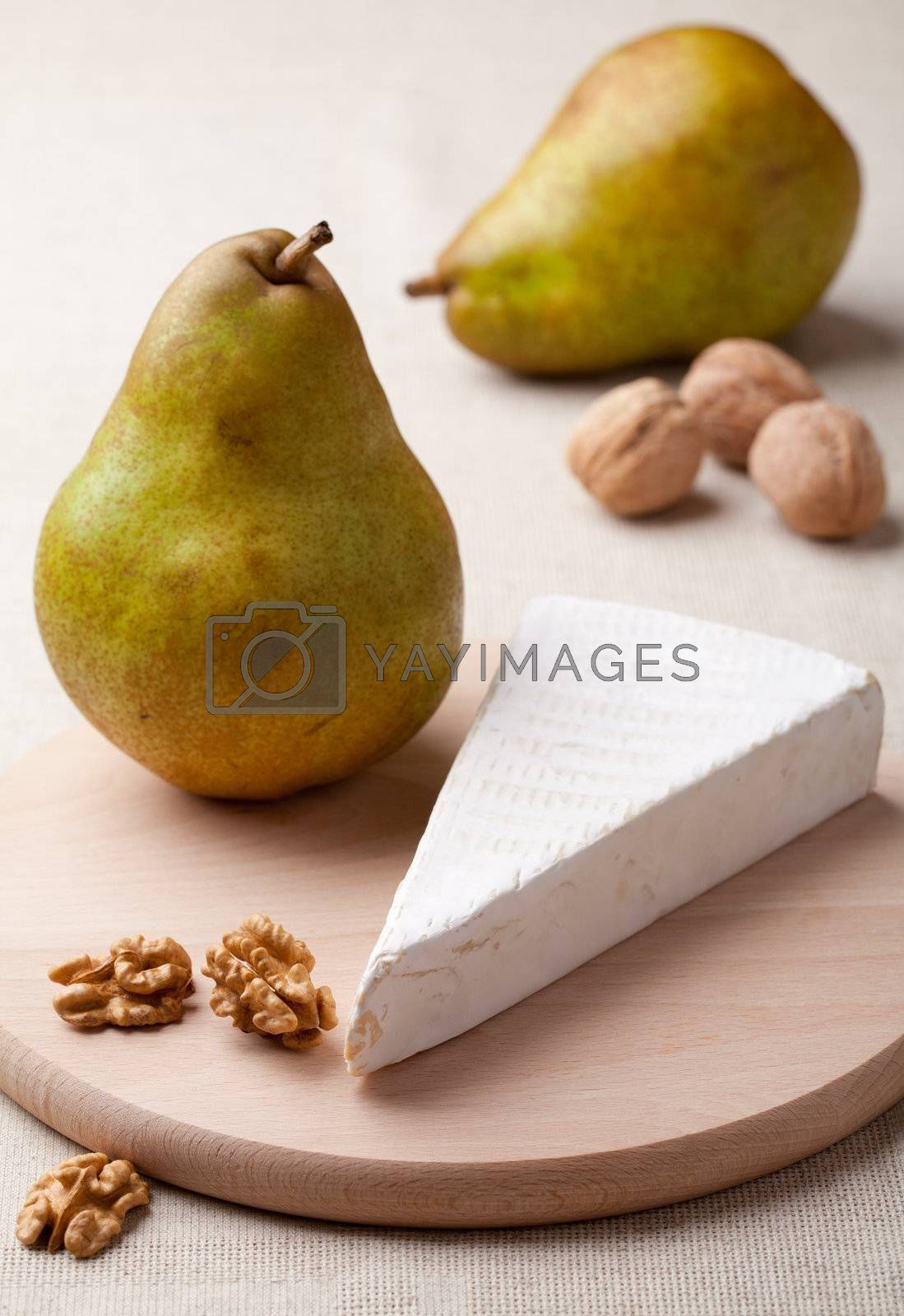 Royalty free image of Green pears, cheese brie, cores of walnuts on wooden board by SergeyAK