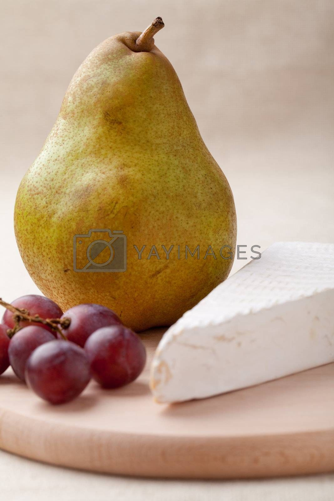 Royalty free image of Green pear, cheese brie, red grapes on wooden board macro by SergeyAK