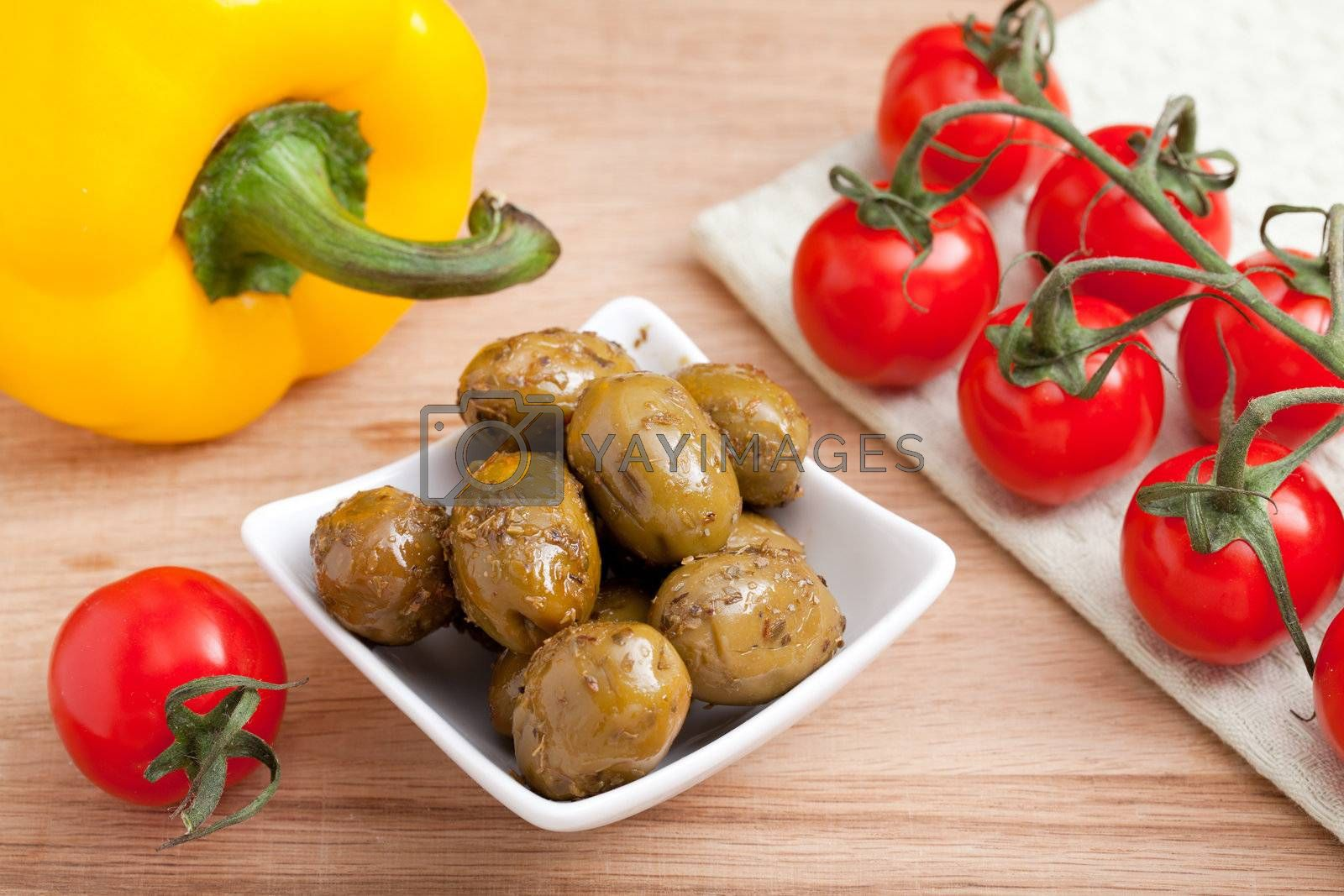 Bunch of ripe red cherry tomatoes  on white napkin, green olives in white glass salad bowl close-up and yellow paprika on wooden table