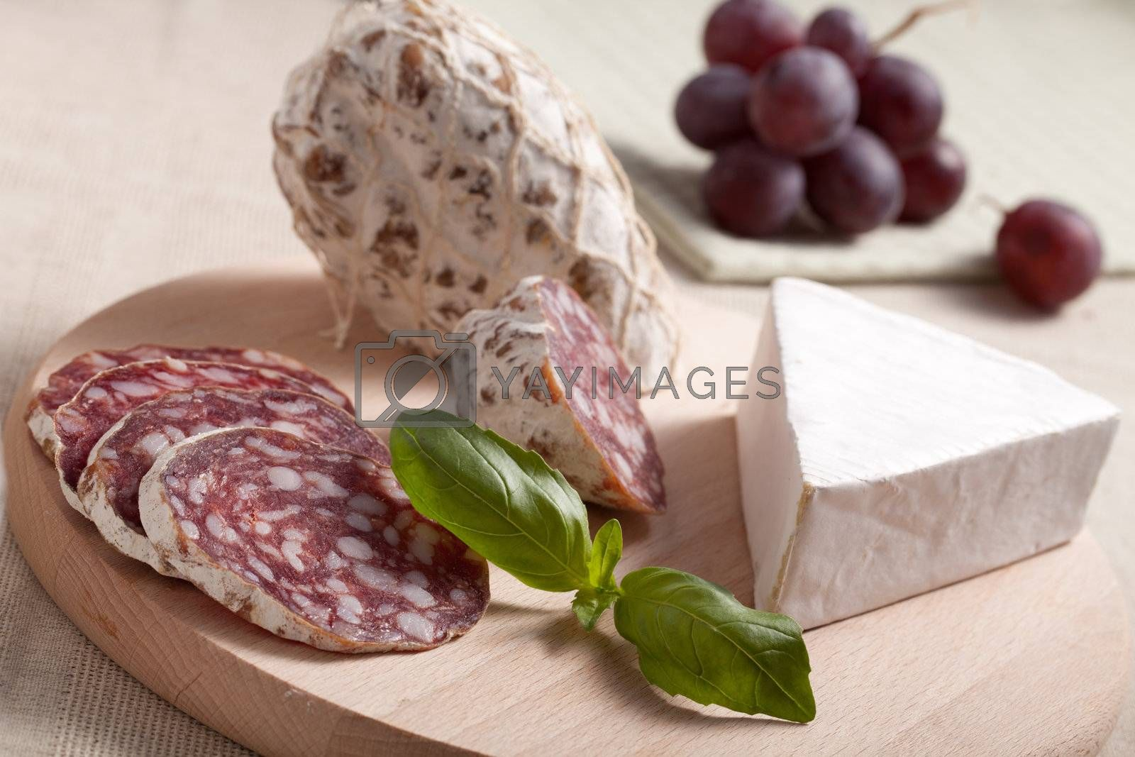 Close-up Traditional sliced meat sausage salami on wooden board with triangular soft cheese brie, green basil and bunch of grapes on textile towel