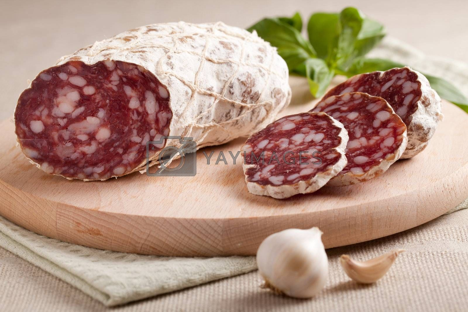 Close-up traditional sliced meat sausage salami on wooden board with head of garlic and green herbs on textile towel