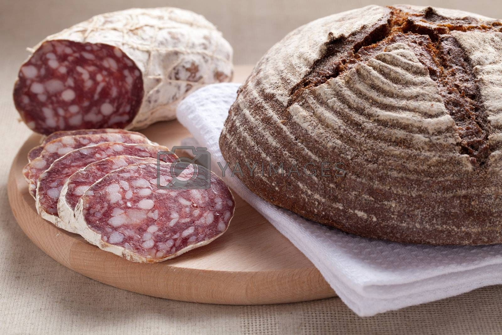 Royalty free image of Traditional sliced salami on wooden board with brown bread by SergeyAK