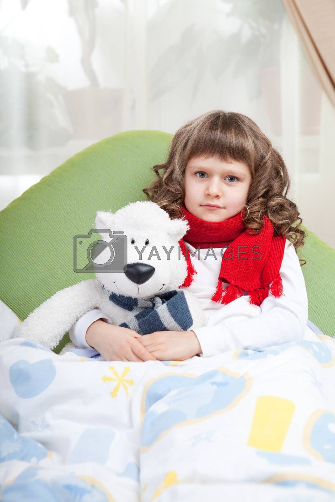 Royalty free image of Little sick girl with scarf embraces toy bear in bed by SergeyAK