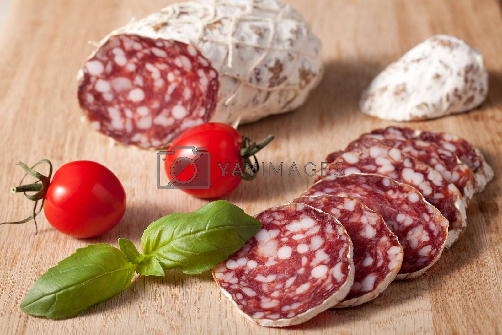 Traditional sliced salami on wooden board with basilic, cherry t by SergeyAK