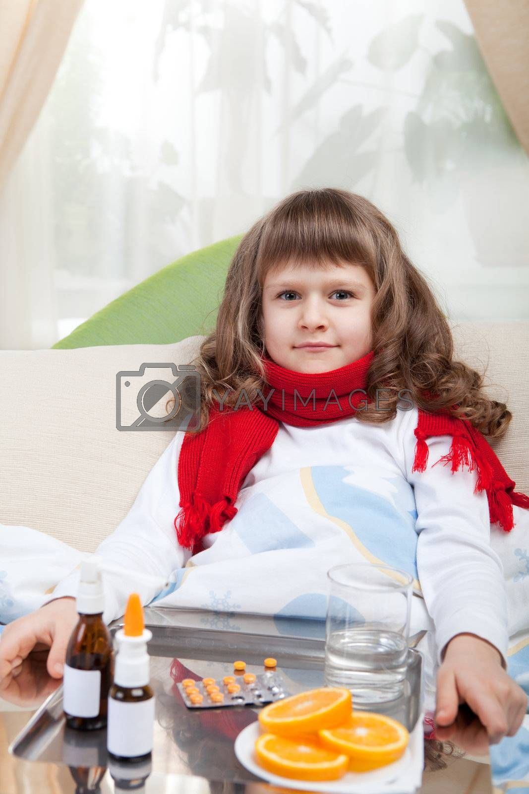 Sympathetic little sick girl in red scarf under blanket in bed is taking a salver with pills, sprays and orange