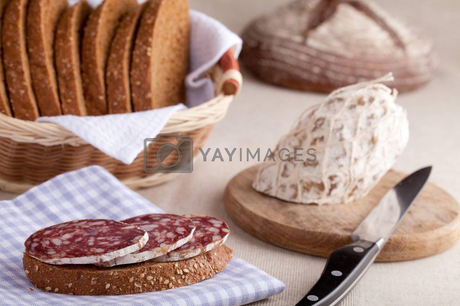 Served kitchen table, sandwich on napkin, salami, breadbasket, s by SergeyAK