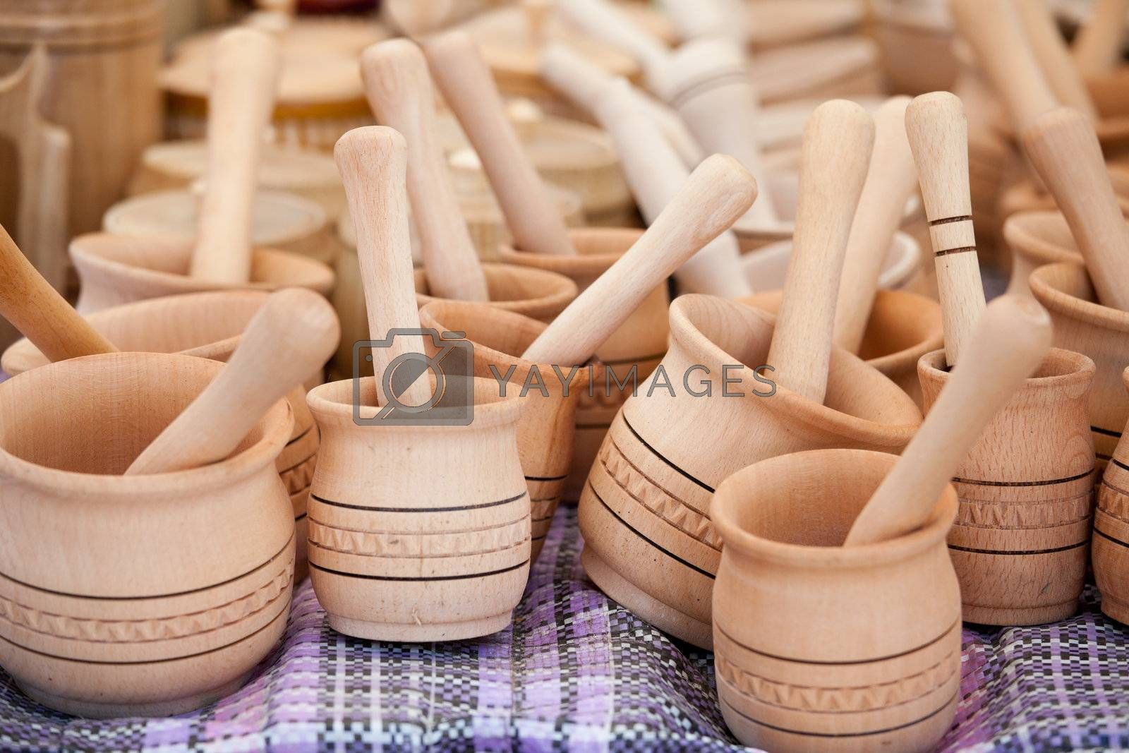 Rustic handmade wooden pounder and pestle on woven towel at street handicraft market