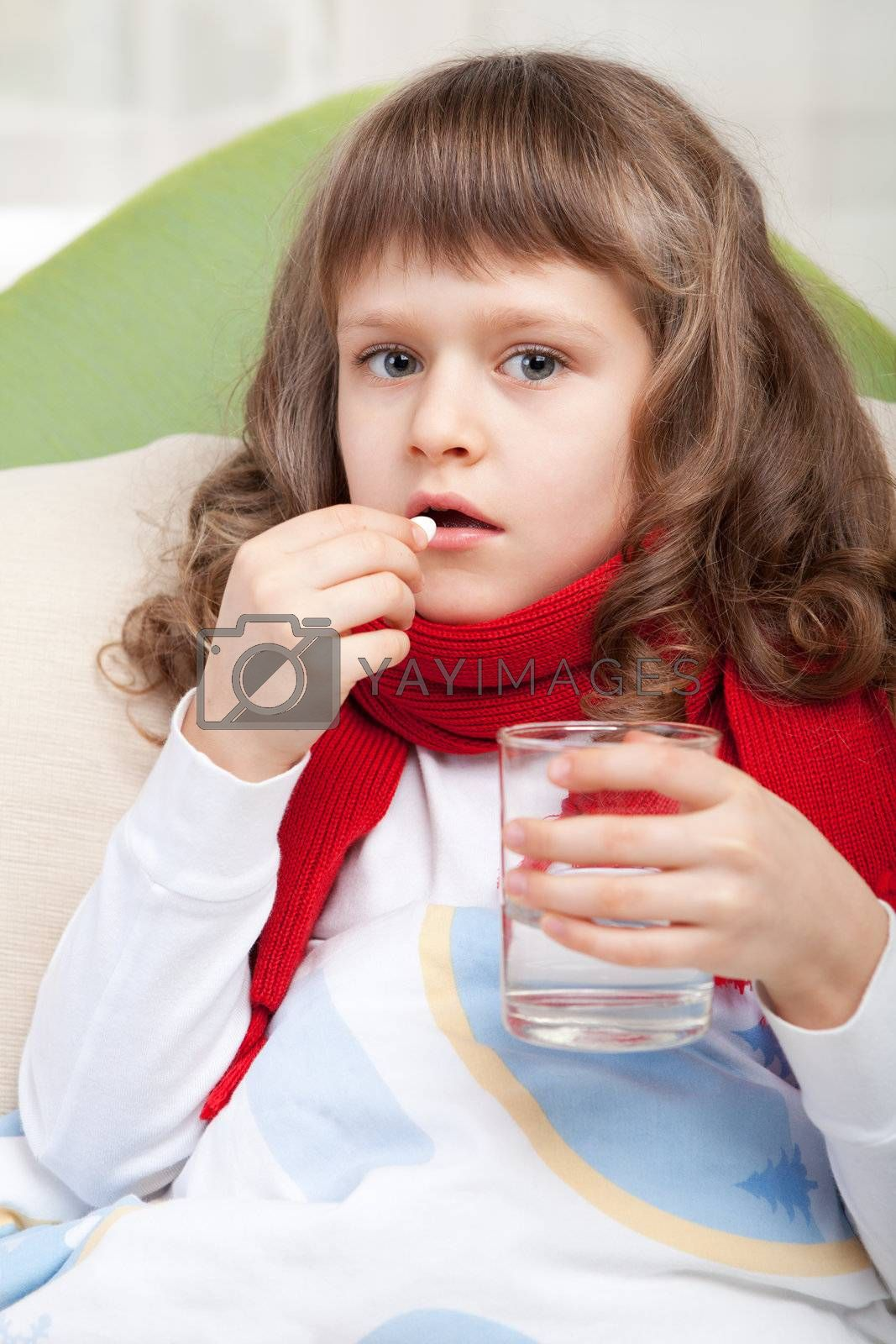 Close-up sympathetic little sick girl wrapped in red scarf under blanket in bed is taking the pill and glass of water