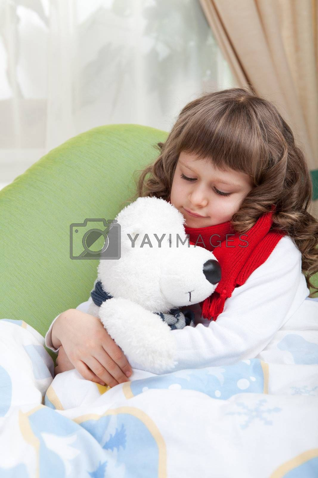 Sympathetic little sick girl with red scarf embraces white toy bear under blanket in bed