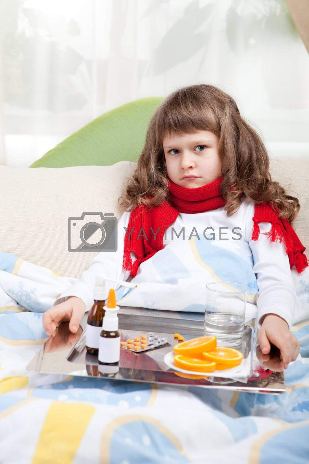 Royalty free image of Little sick girl with scarf in bed is taking medicine by SergeyAK