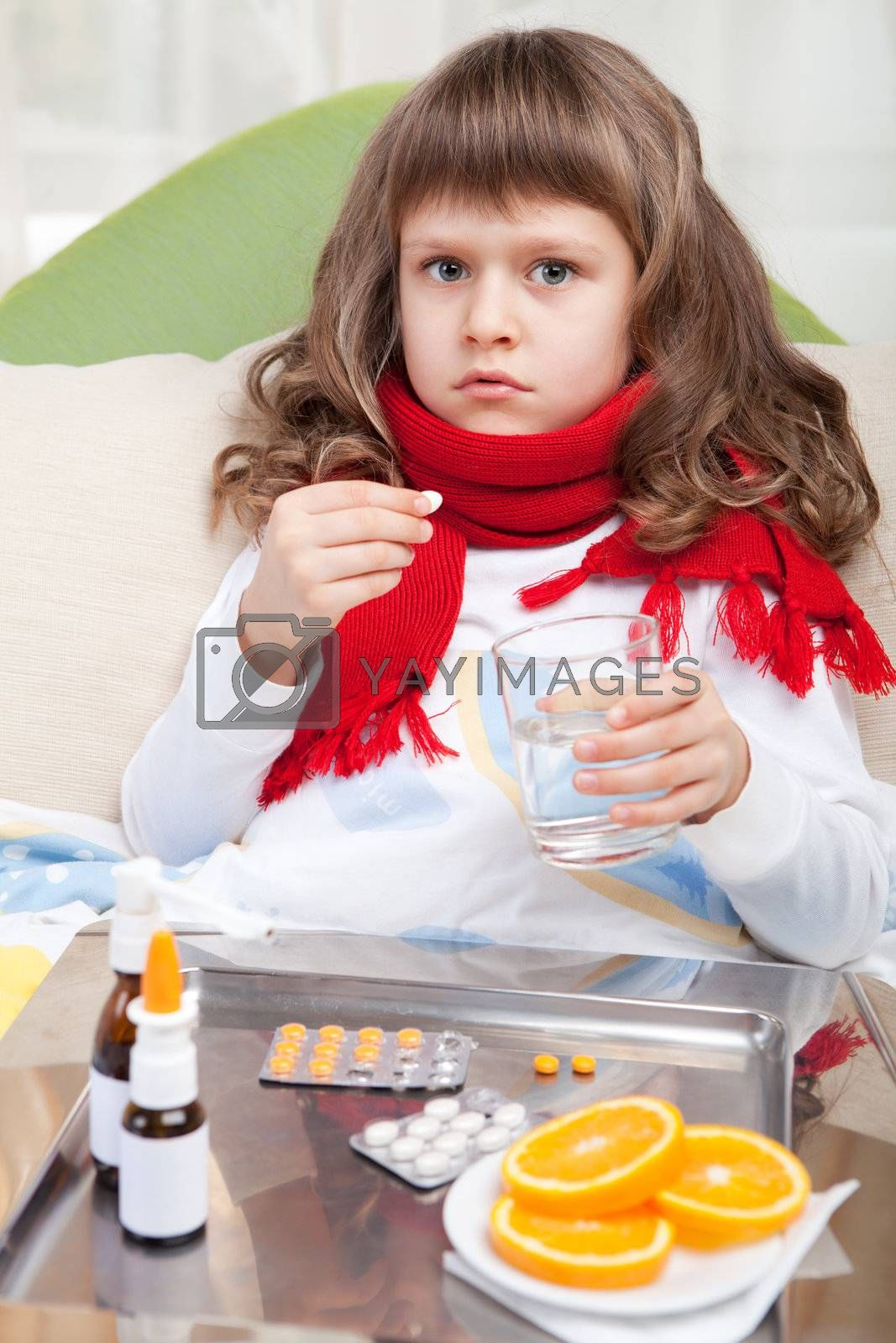 Sympathetic little sick girl wrapped in red scarf is taking a pill and a salver with pills, sprays and orange on the blanket in the bed