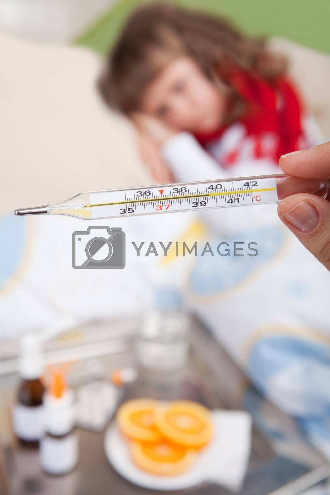 Close-up clinical thermometer in woman's hand showing fever and little sick girl wrapped in red scarf under blanket in the bed and tray with pills, sprays, oranges and glass of water
