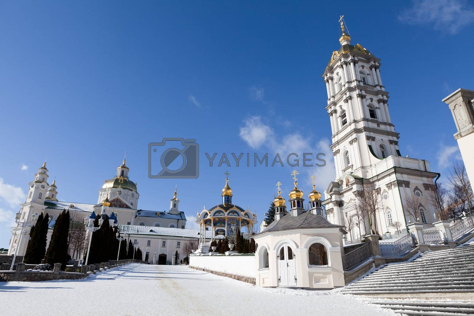 Belfry, dome and church of ancient sacred Christian Pochaev Monastery of Holy Dormition on blue sky background. Western Ukraine, Ternopol region, 16th century