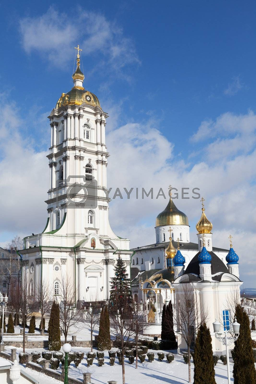 Belfry, dome and church of ancient sacred Christian Pochaev Monastery of Holy Dormition on blue cloudy sky background. Western Ukraine, Ternopol region, 16th century