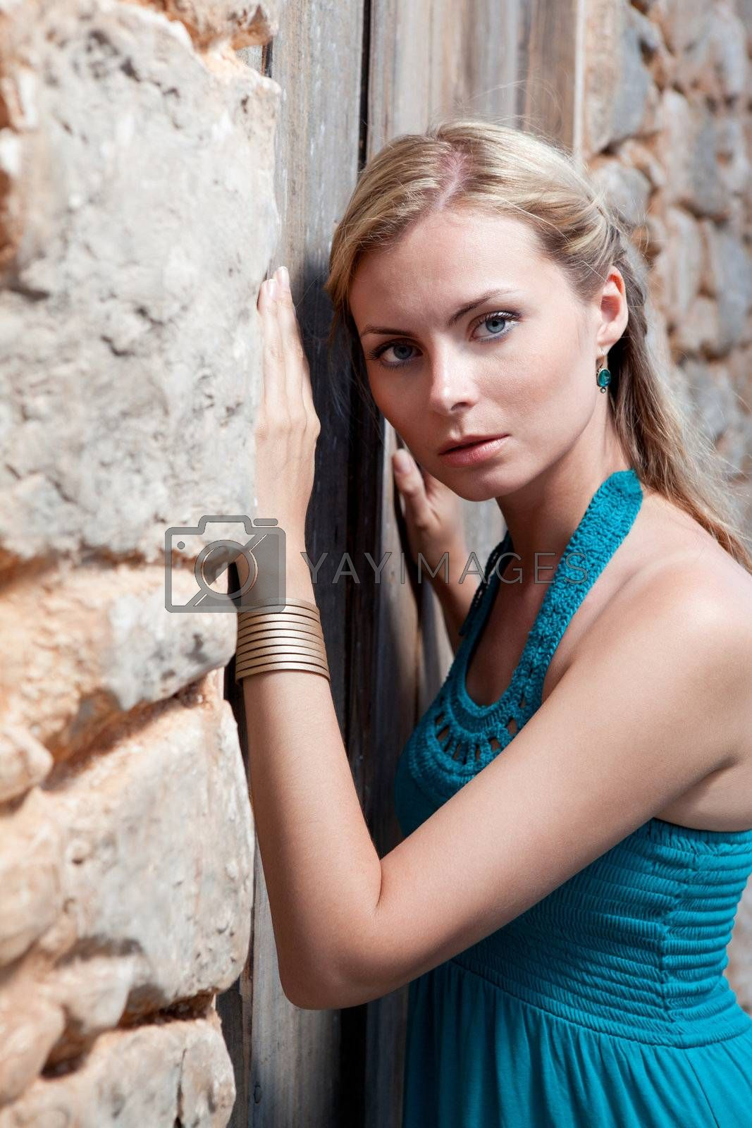 Romantic young blond woman in blue on stone wall background by SergeyAK