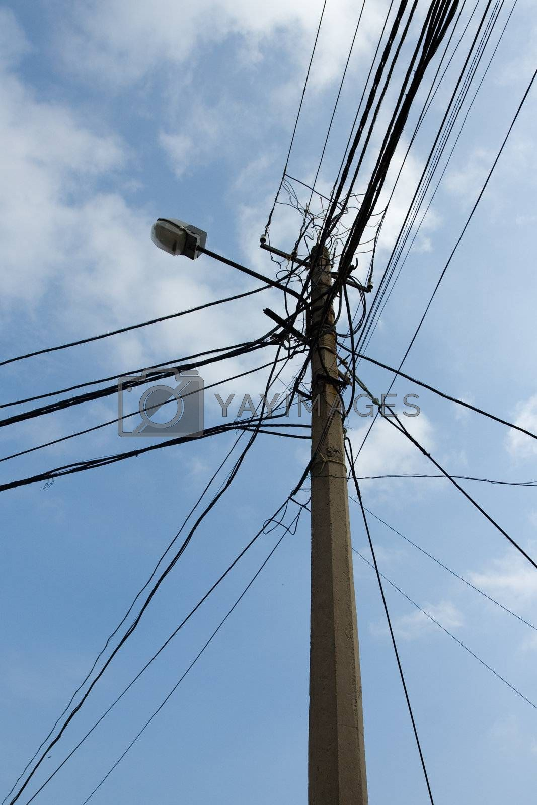 Lamp pole and tangled electric wires on the blue sky background. Vertical