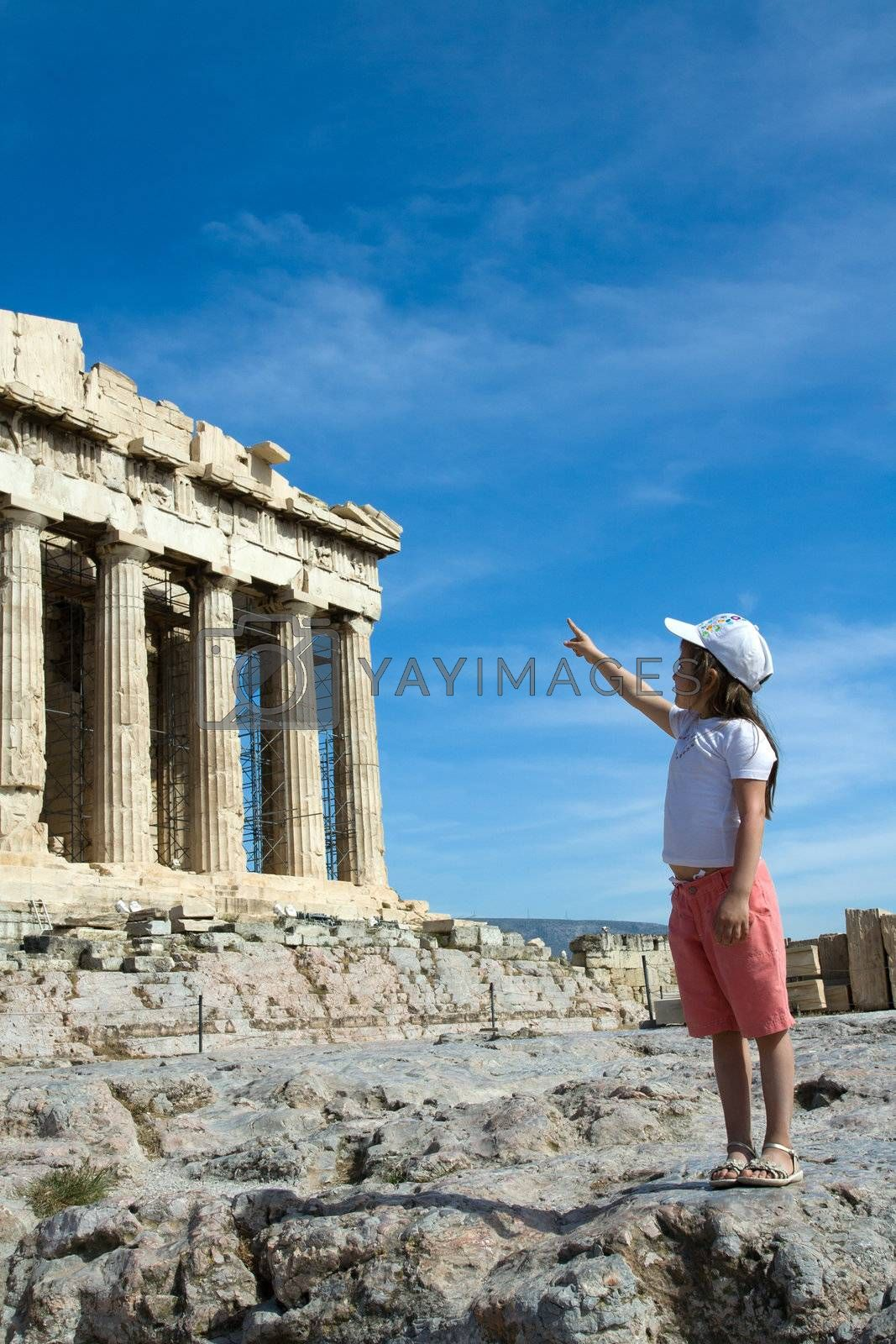 Little Child points to Facade of ancient temple Parthenon in Acropolis Athens Greece on the blue sky background