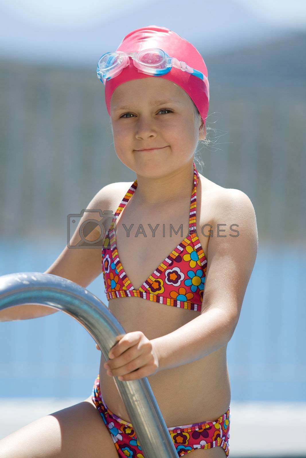 Close-up portrait of smiling cute little child in bathing cap, glasses near swimming pool stairs