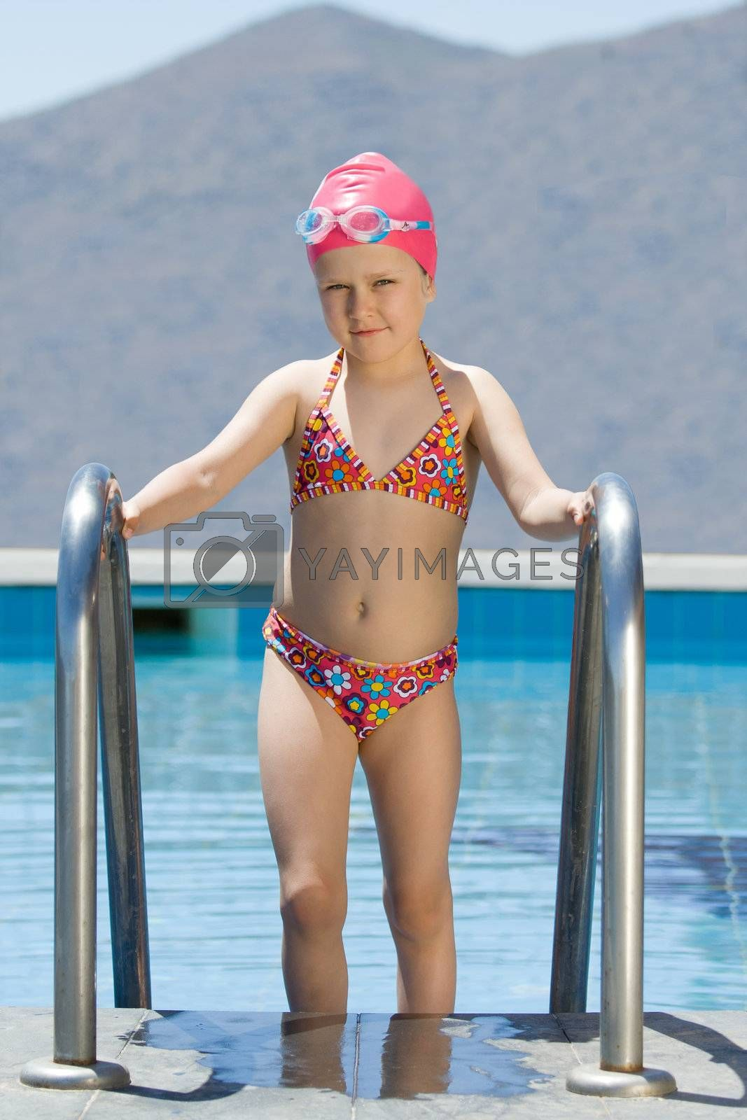 Smiling cute little girl in bathing cap and glasses walks up the swimming pool stairs