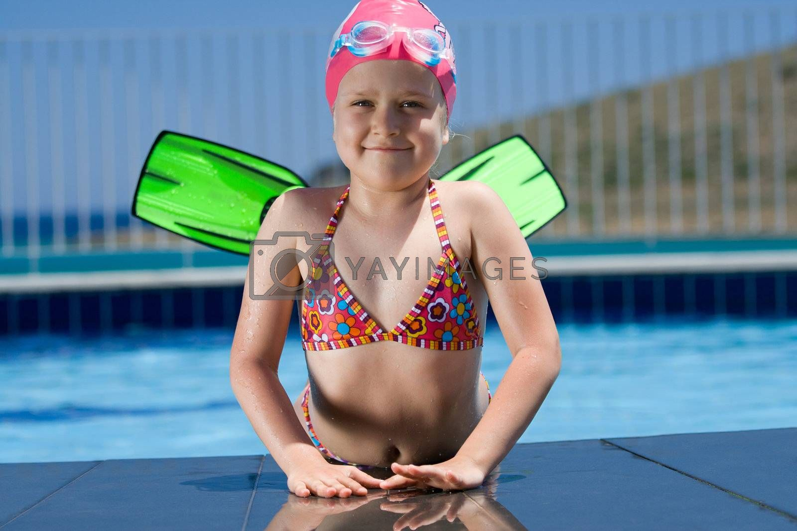 Close-up portrait of smiling cute little child in bathing cap, glasses and fins is lying on the swimming pool ledge