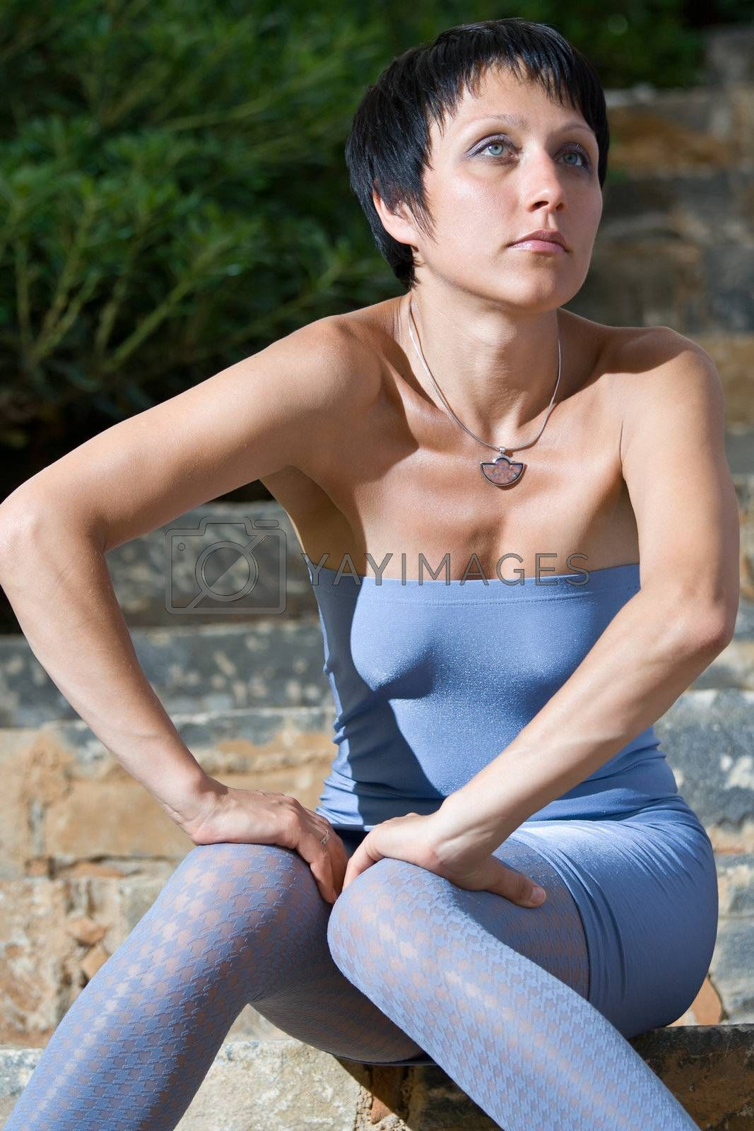 Close-up portrait of young tempting attractive romantic fashion sensual sexy brunette woman in light blue skintight evening dress and tights is sitting on the stone steps