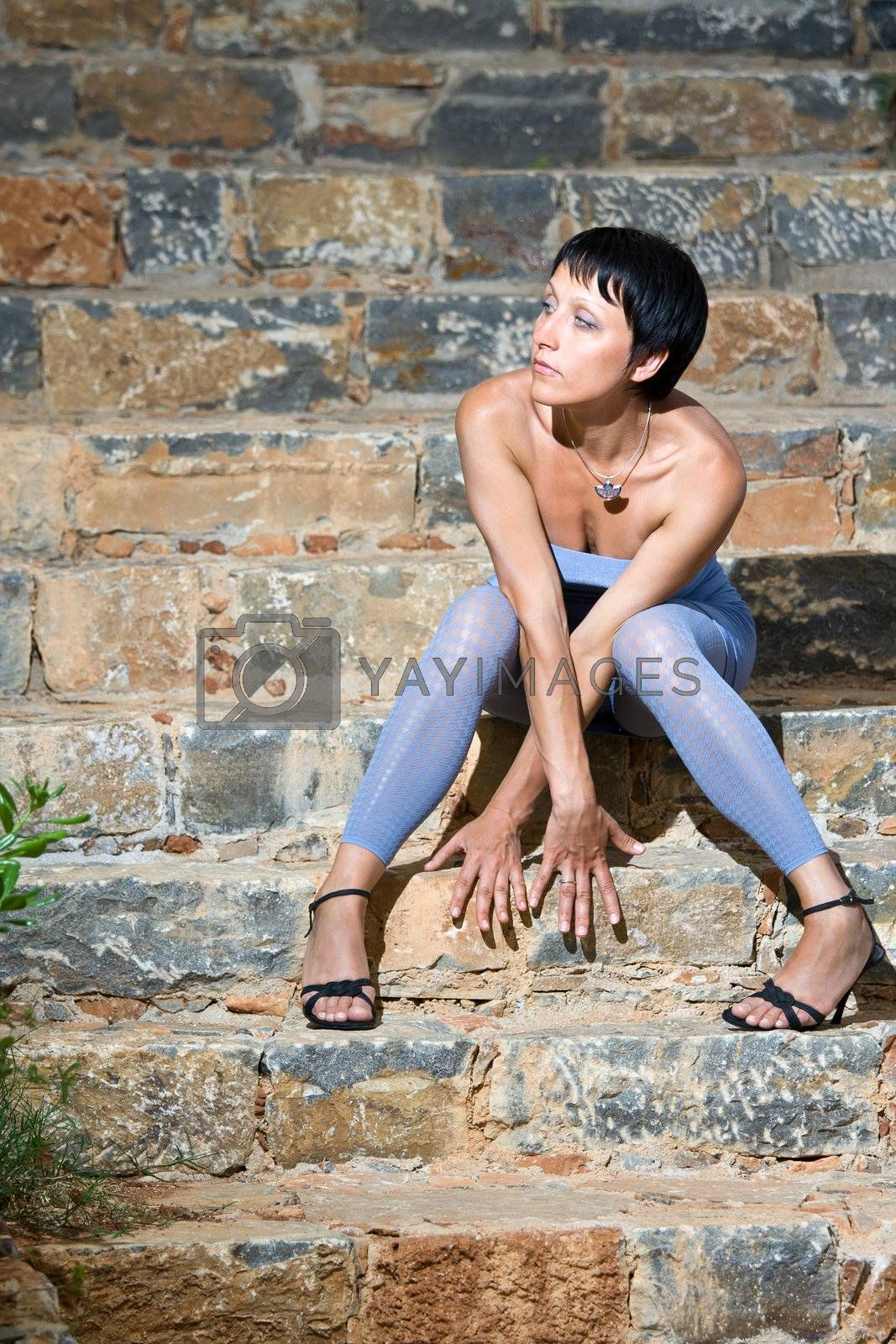 Portrait of young tempting attractive romantic fashion sensual sexy beautiful brunette woman in light blue skintight evening dress and leggings is sitting on the stone steps