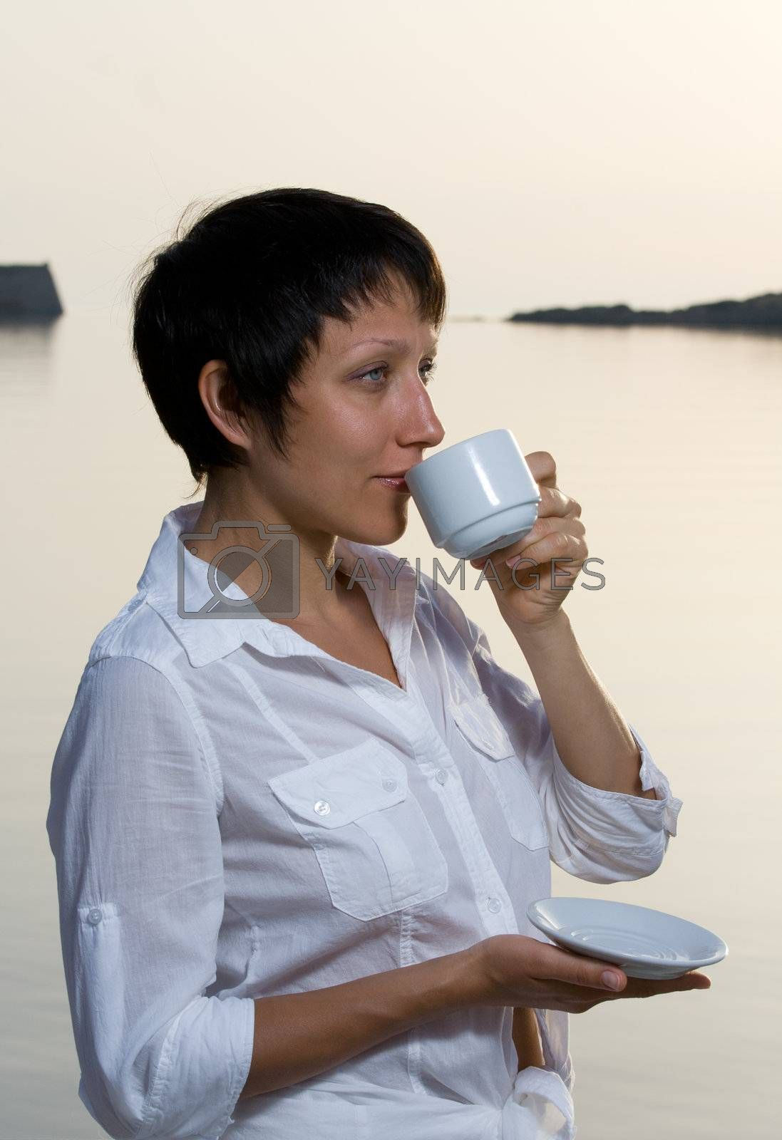 Young woman meets sunrise drinking morning coffee  by SergeyAK