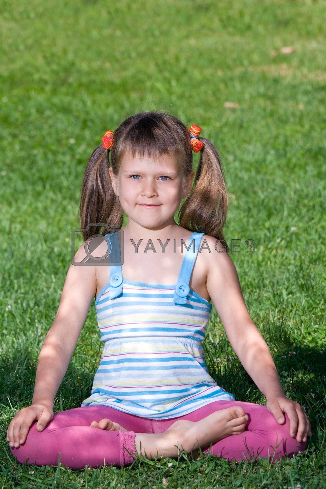 Smiling child sit and meditate in asana on green grass by SergeyAK
