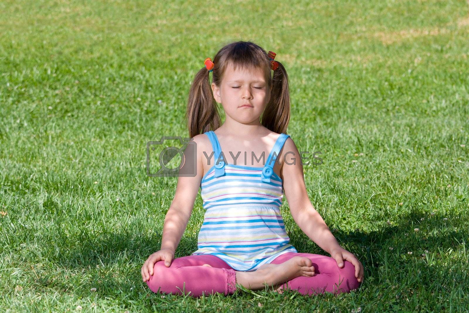 Healthy lifestyle. Little cute girl who is sitting and meditating in asana under tree shadow with closed eyes on the green grass