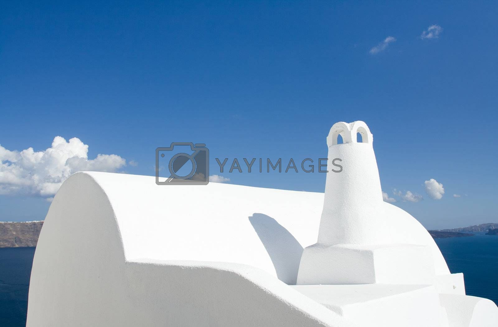 Old-style white traditional Greek roof and chimney in village Oia of Cyclades island Santorini Greece on the blue Aegean Sea and cloudy sky background