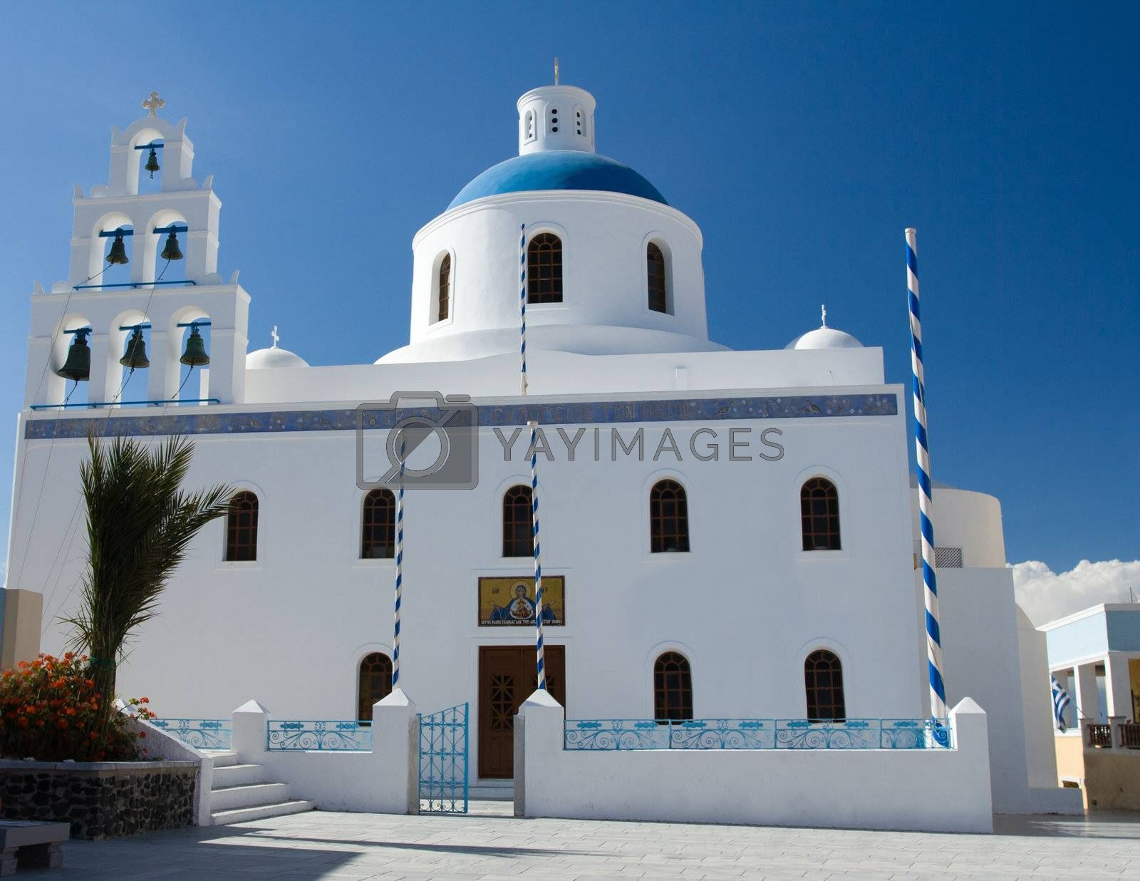 Belfry and cupola of traditional old style white Church of panagia of platsani on Caldera Square in village Oia of Cyclades Island Santorini Greece on the blue sky background