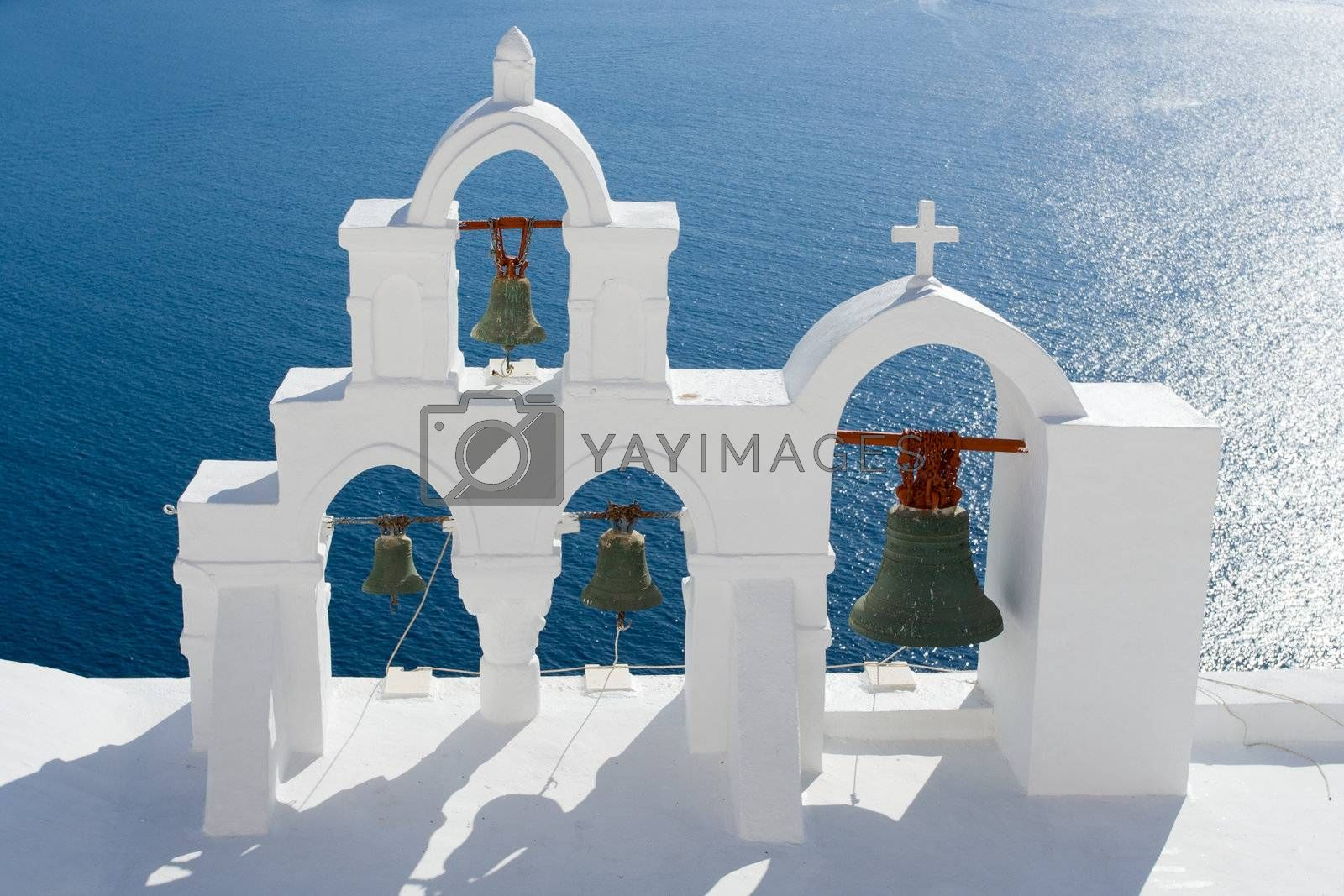 View on calm sea surface through traditional Greek white church arch with cross and bells in village Oia of Cyclades Island Santorini Greece