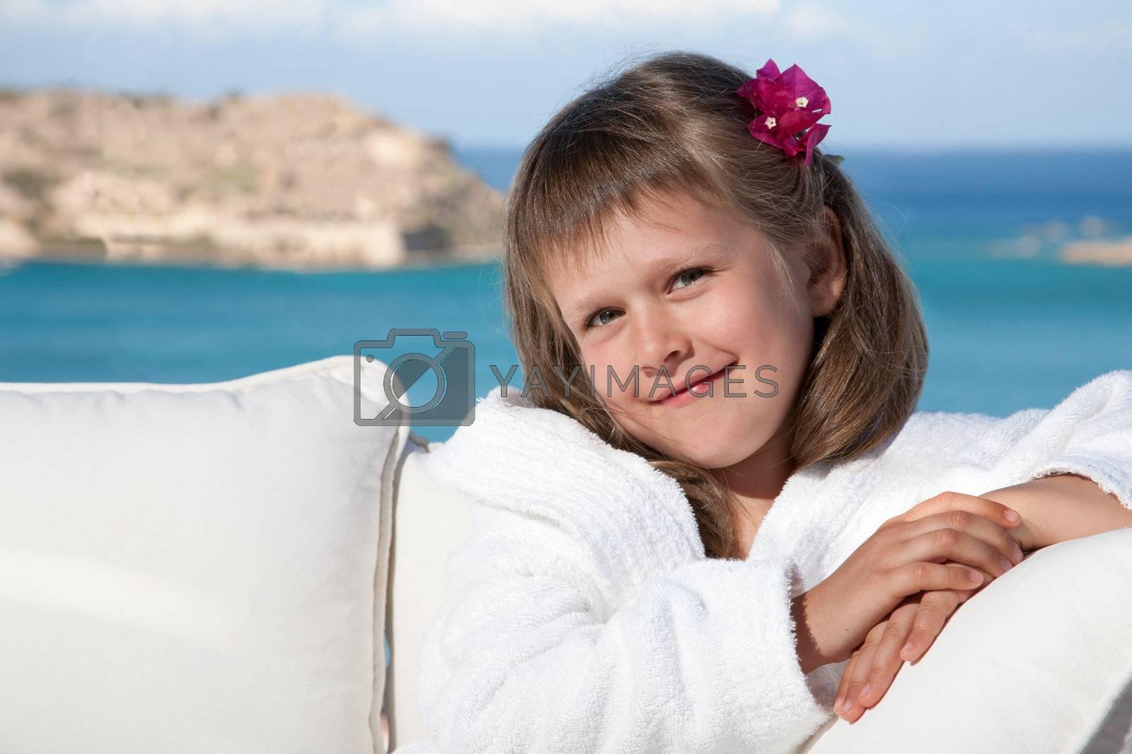 Little girl in white bathrobe relaxing on terrace sea background by SergeyAK