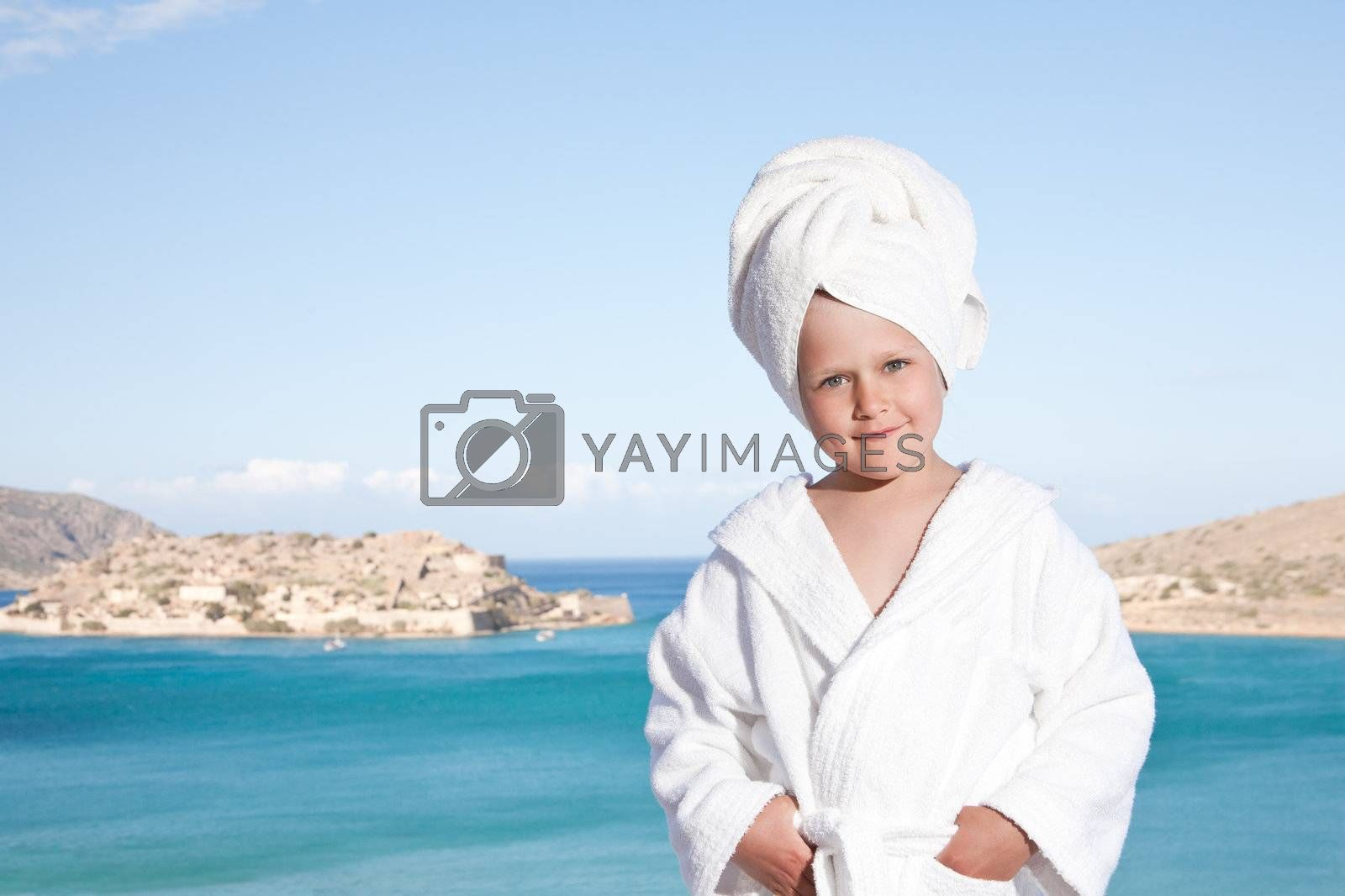Portrait of happy smiling little girl with towel on the head in white bathrobe relaxing on terrace and looking at camera on the sea background