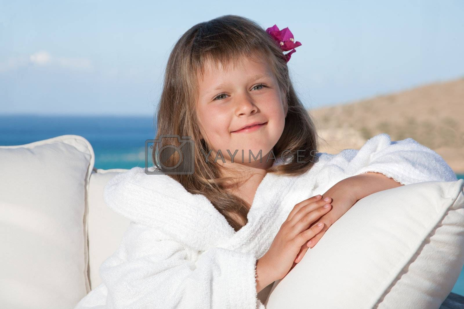 Little girl in white bathrobe relaxing on terrace sea background by SergeyAK