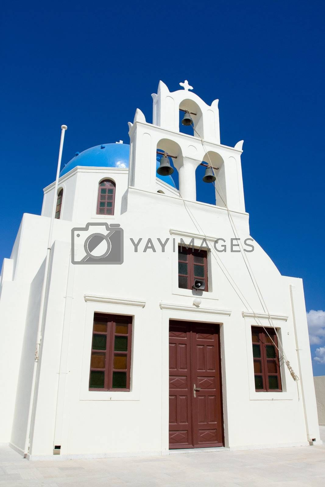 Entrance in traditional Greek white church, archs with cross and bells in village Oia of Cyclades Island Santorini Greece