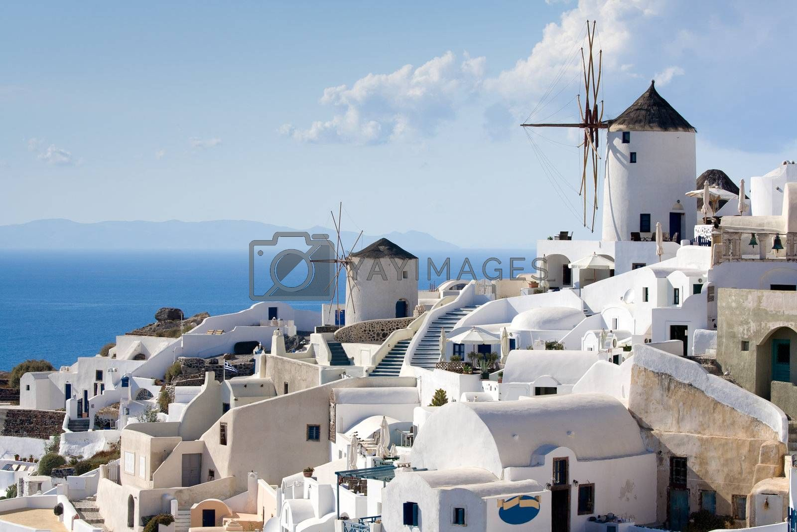 Old-style white traditional windmills in terraced village Oia of Cyclades island Santorini Greece on the blue Aegean Sea and sky background