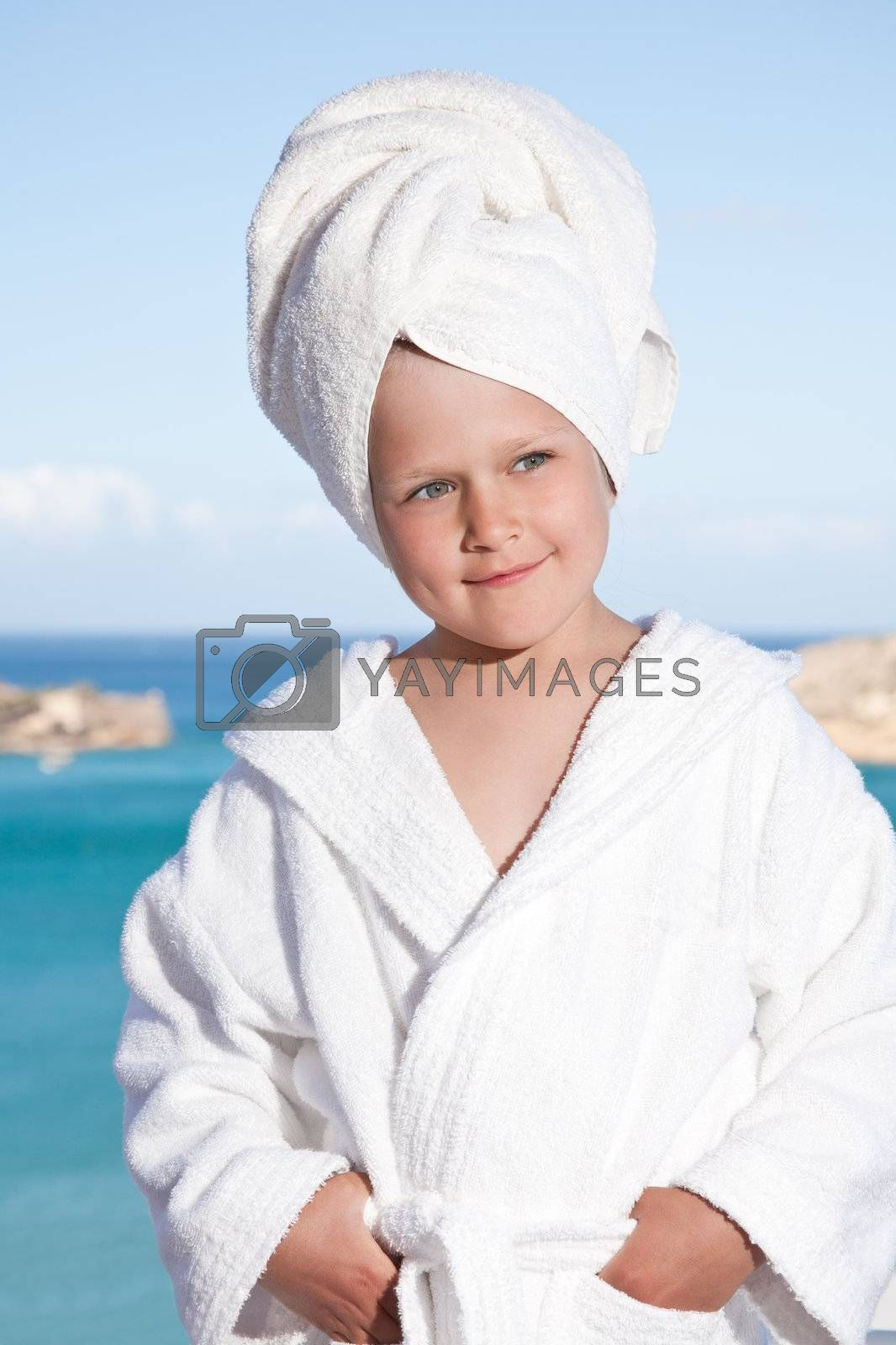 Portrait of happy smiling little girl with towel on the head in white bathrobe relaxing on terrace on the sea background