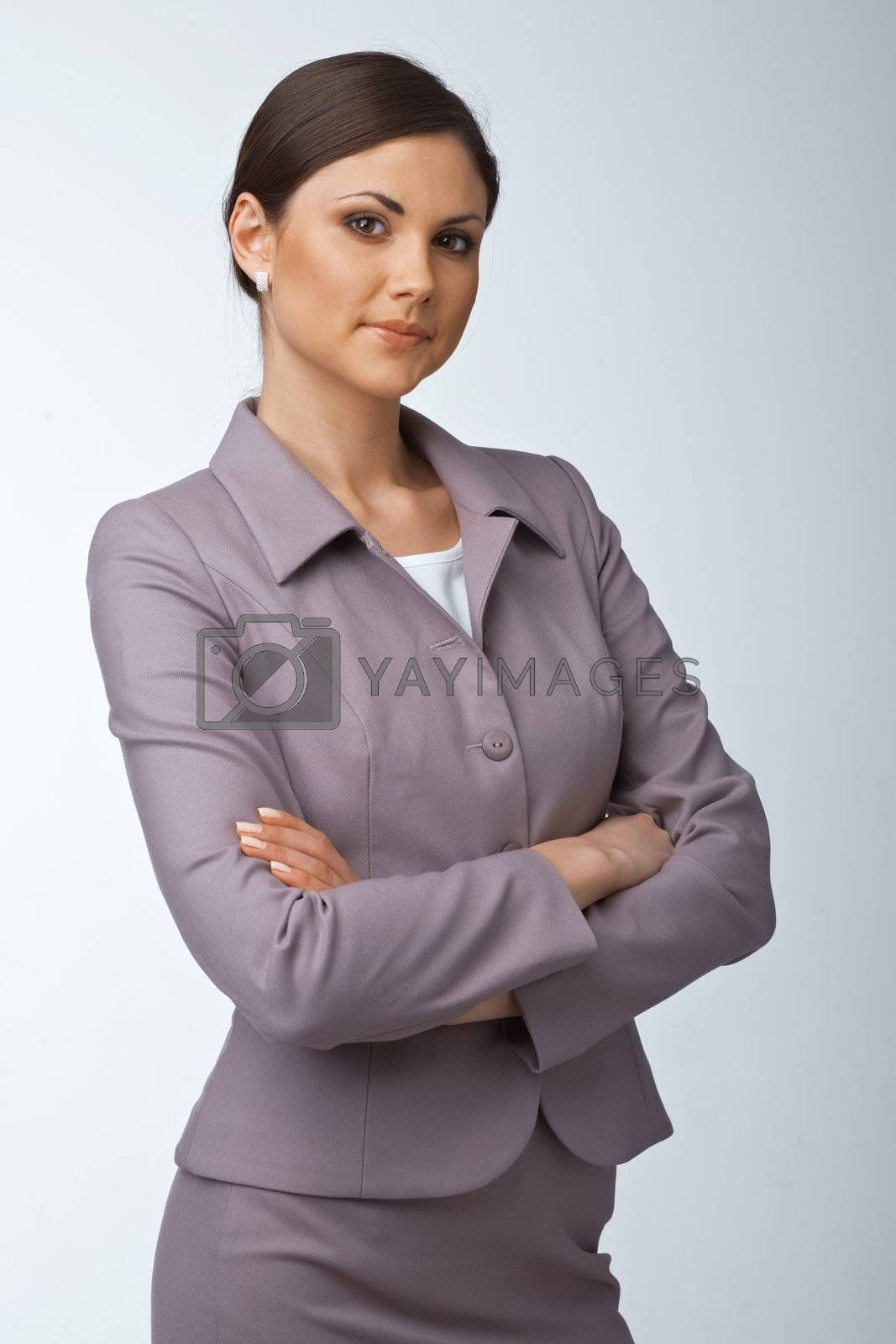 Pretty young business woman with hands folded looking at you on white background