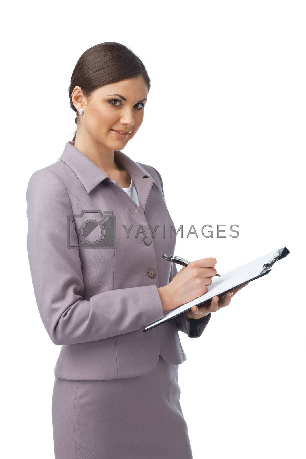 Portrait of a young businesswoman writing something in her folder and smiling