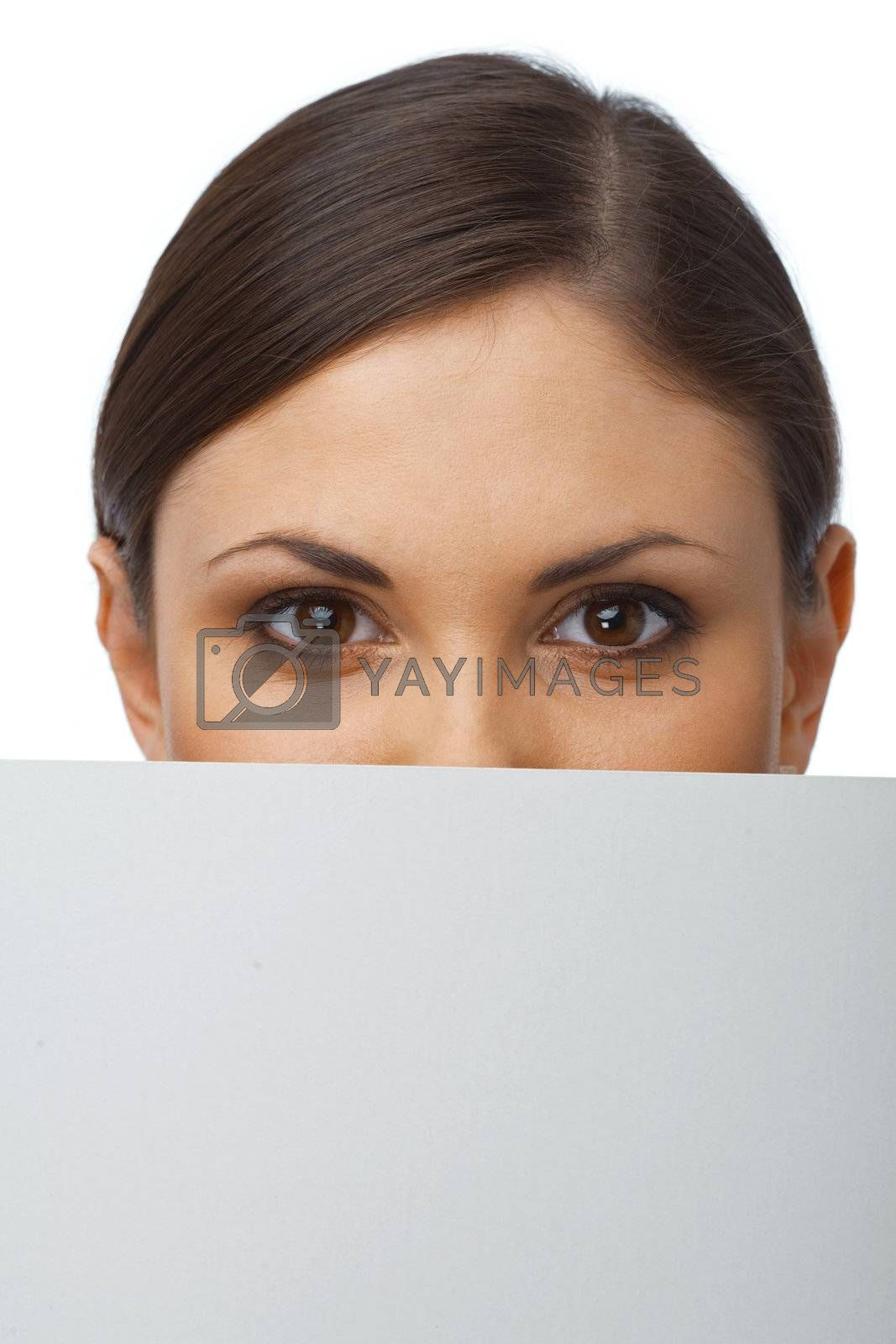 Close up portrait of a young girl hiding behind the blank billboard