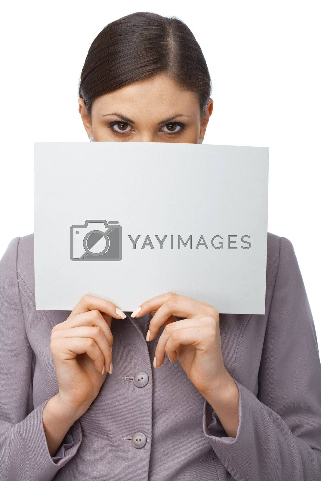 Closeup portrait of a young girl hiding behind an empty white billboard , isolated on white