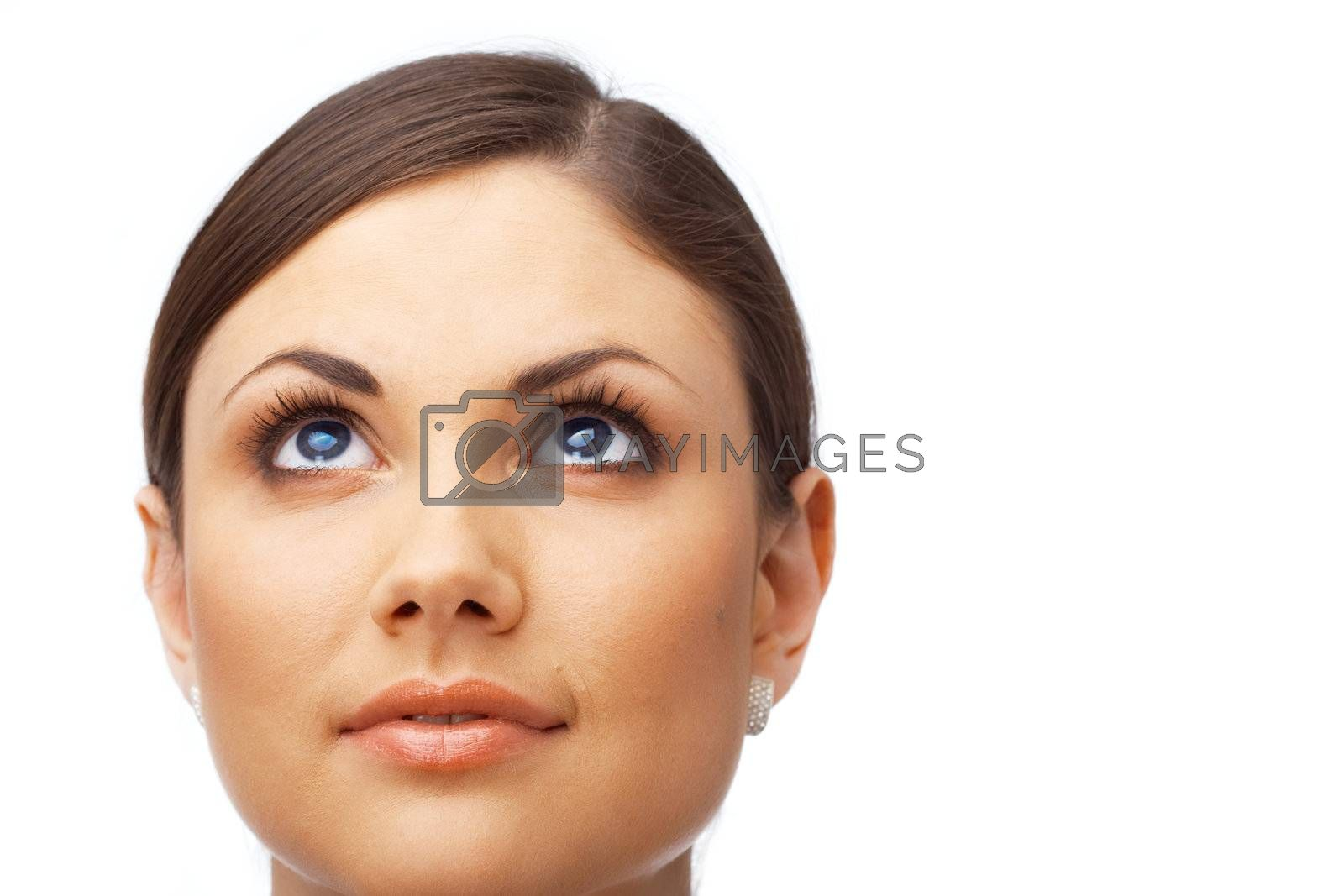 Closeup of a thoughtful young woman looking up over white background