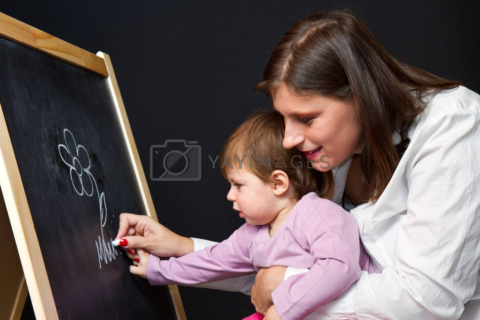 Mother and little daughter writing on a blackboard by lsantilli