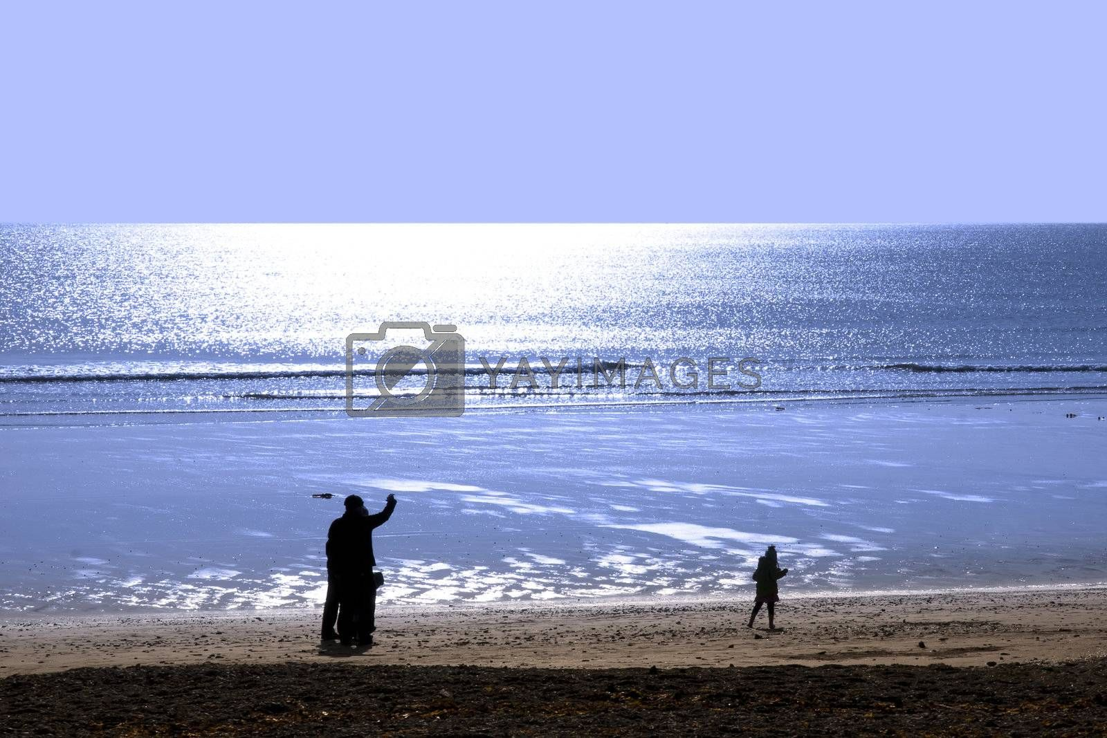 family strolling along the beach before sunset in Ballybunion county Kerry Ireland