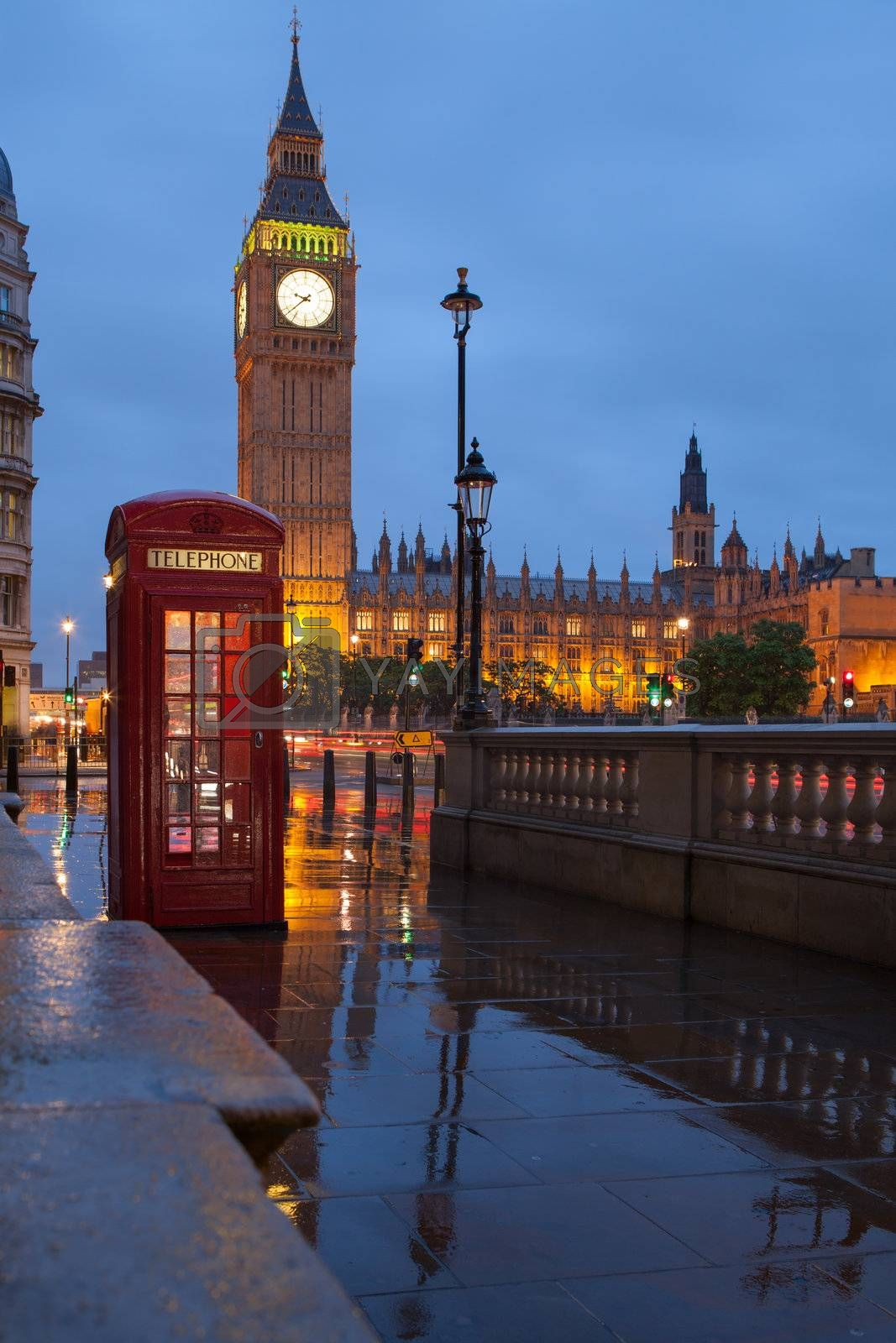 Red public telephone box and illuminated clock on Big Ben tower of Westminster Palace in twilight with reflection on wet footway, Great Britain