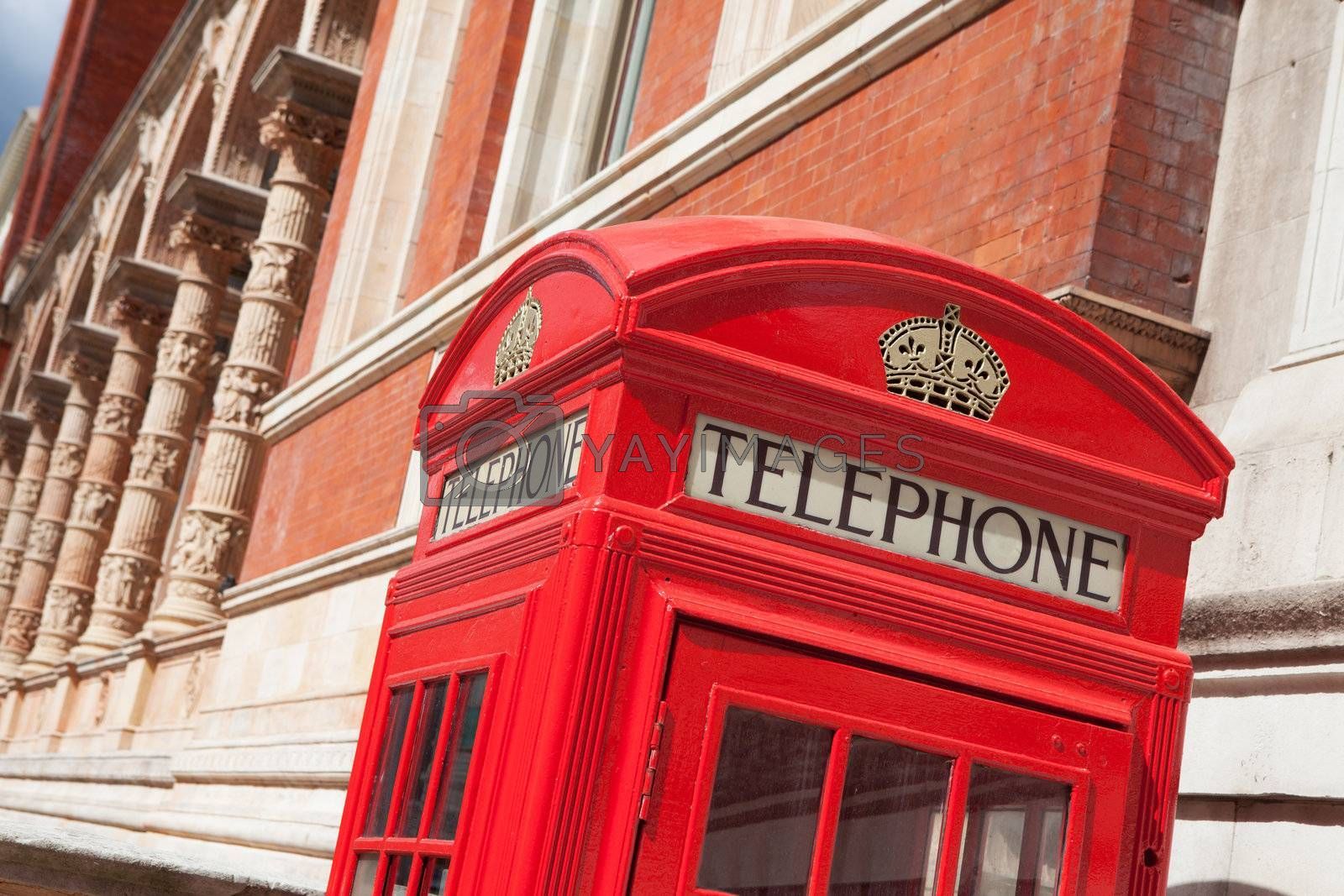 Traditional London symbol red public phone box on building facade background, Great Britain
