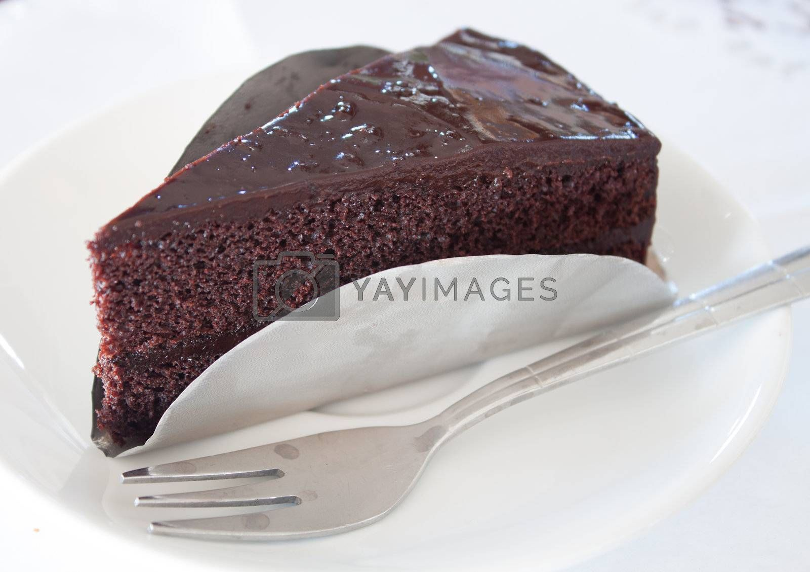 A piece of dark chocolate cake on white isolated background